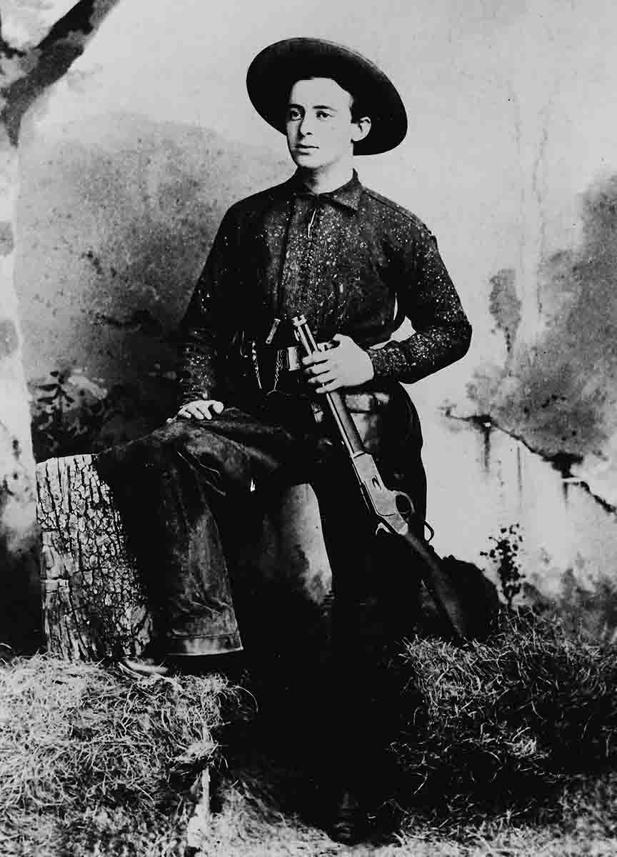 This vintage photo shows a young man with his special order Winchester Model 1873 saddle ring carbine with a barrel measuring less than 20 inches.