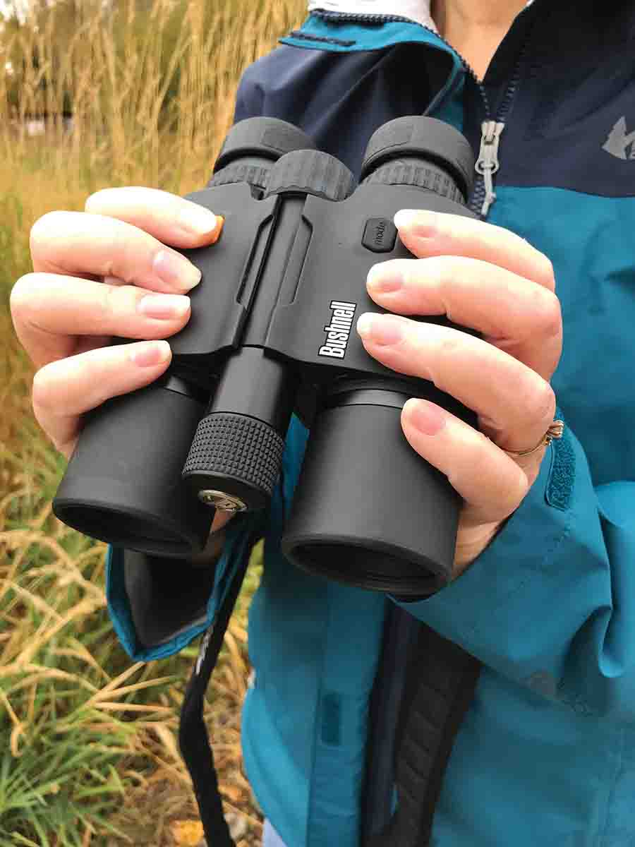 The Bushnell Fusion 10x42mm 1 Mile ARC rangefinding binocular has its orange range/power button placed right where the index finger of the right hand normally grasps a binocular. The battery compartment sticks out between the binocular's barrels.