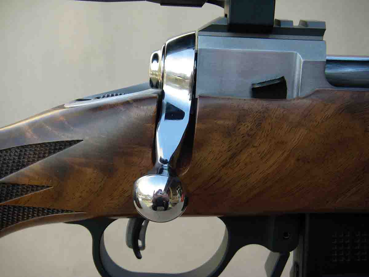 The rifle features a large, brightly polished bolt handle.