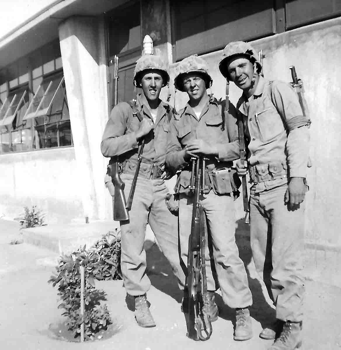 Three U.S. Marines ready to head to Korea in 1950, armed with M1 Garands and a Model 1918A2 BAR.