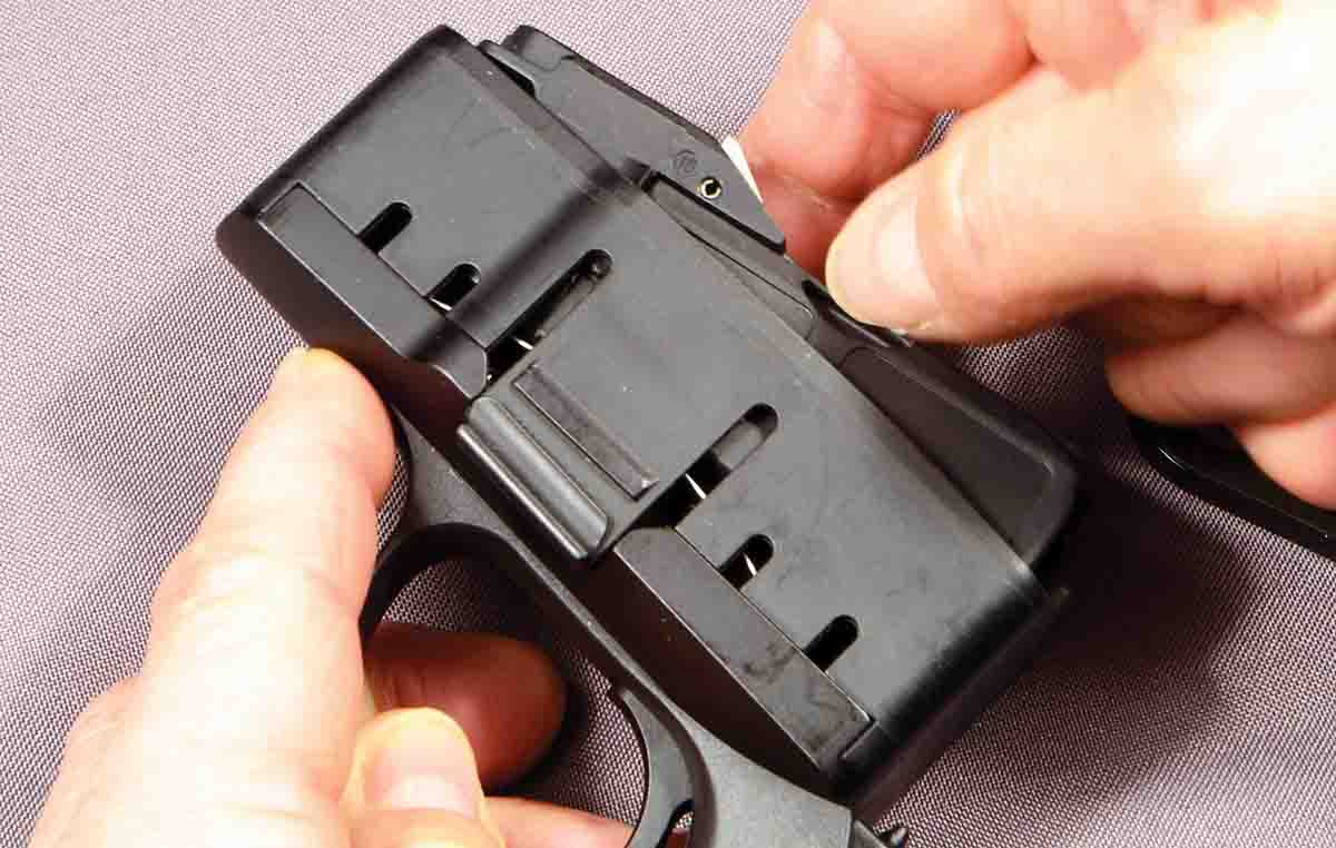 Simply pushing on the thumb slot of the magazine insert releases the locking studs.