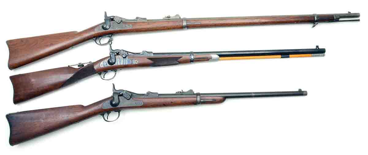 These are the basic configurations of U.S. Model 1873 trapdoor .45s. Top is a standard infantry rifle. Bottom is a standard cavalry carbine. Between them is a replica of the Officer's Model made by the H&R Company in the 1970s.
