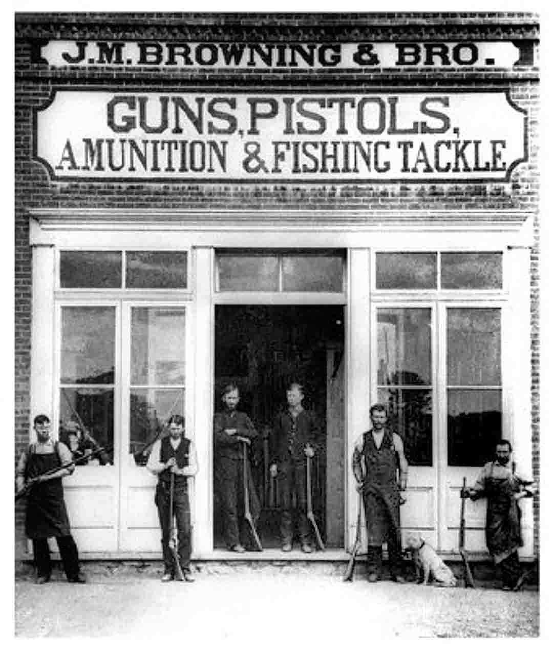 "The Browning store in Utah. Workman are out showing their wares all dressed for a day's work. Note the sign with the misspelling of ""ammunition."""